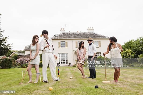 Friends playing croquet in backyard