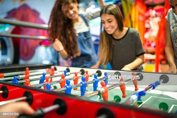 Amigos jugando al fútbol en la galería comercial partido