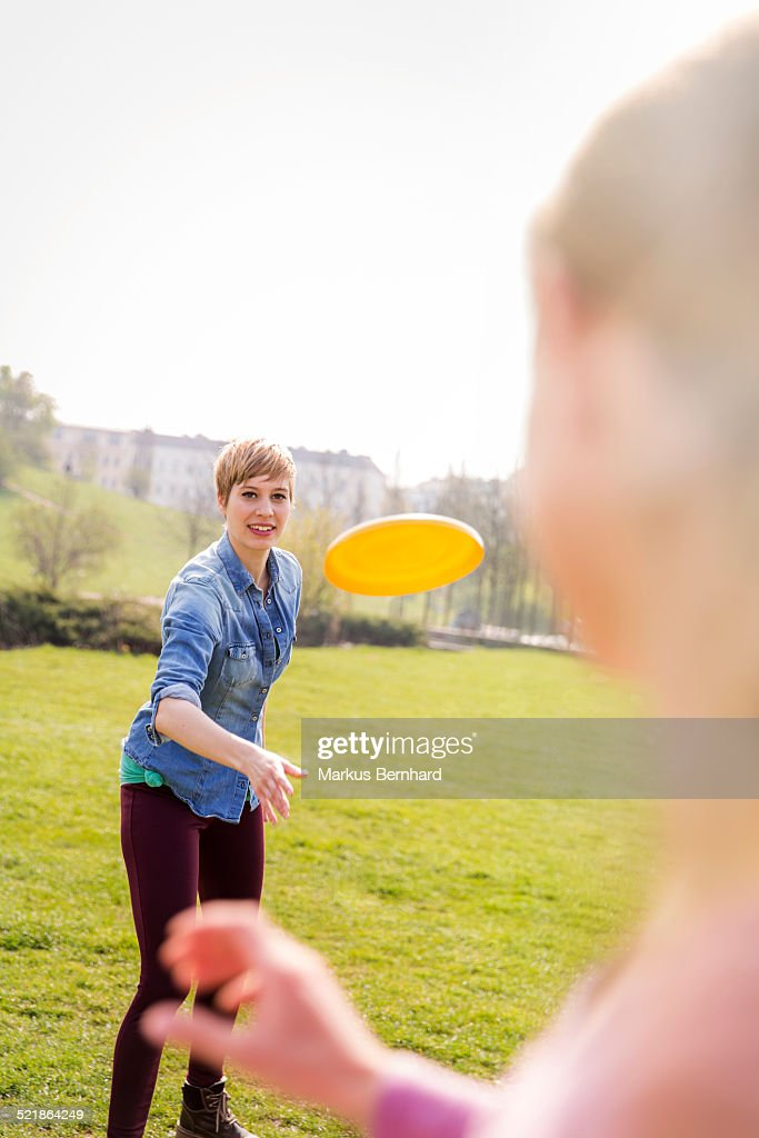 Friends playing frisbee in park