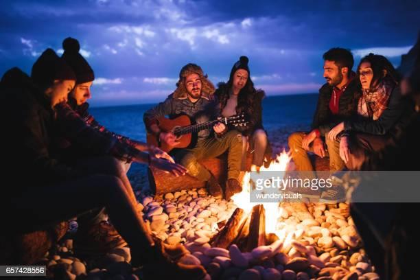 Vrienden gitaar spelen en zingen rond vreugdevuur op het strand