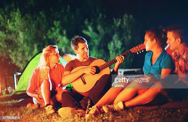 Freunde spielen der Gitarre von Lagerfeuer.
