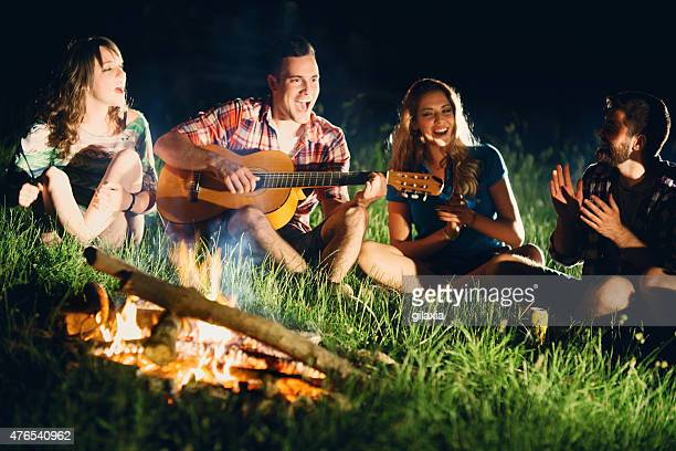 Friends playing guitar gathered around campfire.