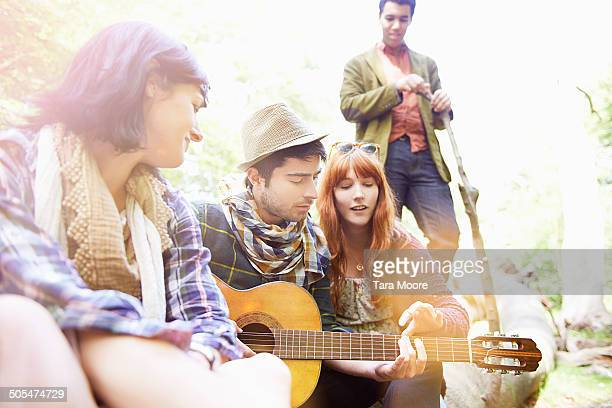 friends playing guitar in park
