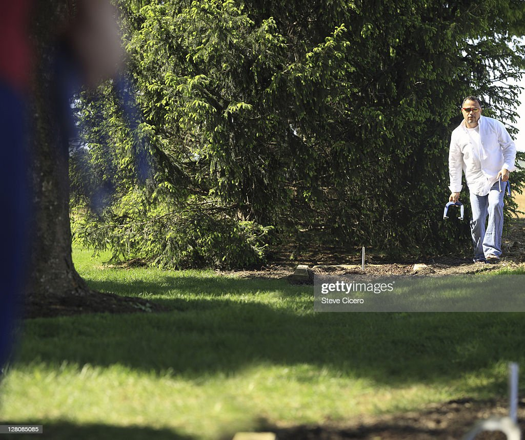friends playing horseshoes in backyard stock photo getty images