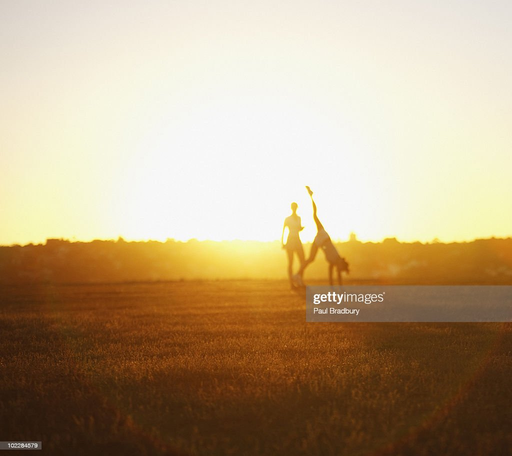 Friends playing in field at sunset : Stock Photo