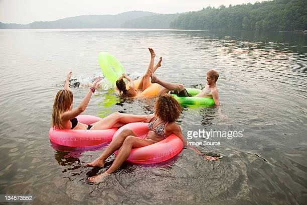 Amis jouant sur des anneaux gonflables sur le lac