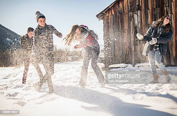 Friends playing in snow outside winter cabin