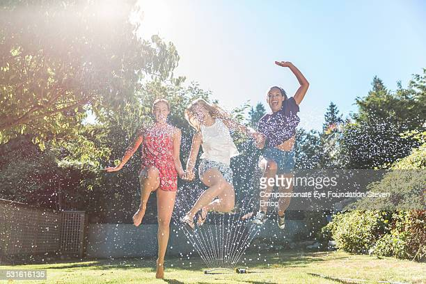 Friends playing in sprinkler in backyard