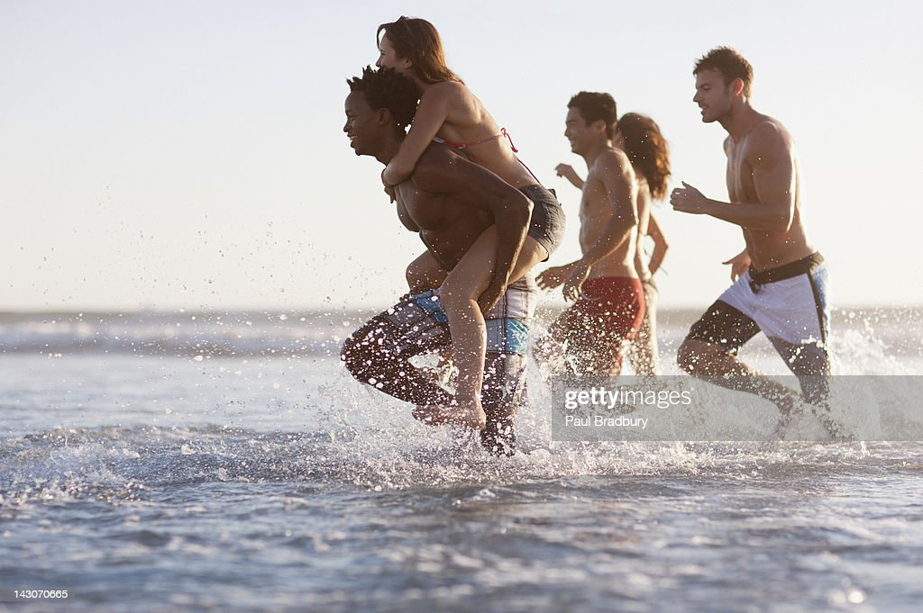 Friends playing in waves at beach : Stock Photo