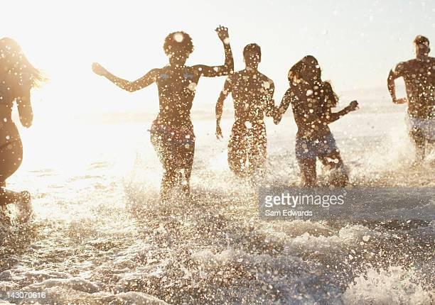 Freunde spielen in den Wellen am Strand