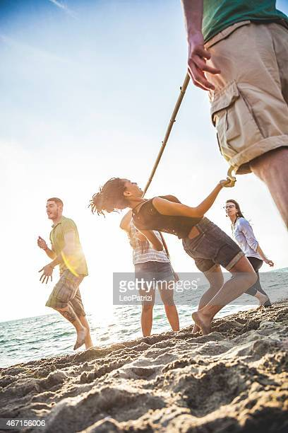 Friends playing limbo on the beach during vacations