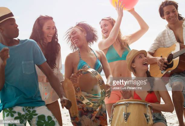 Friends playing music and dancing on beach