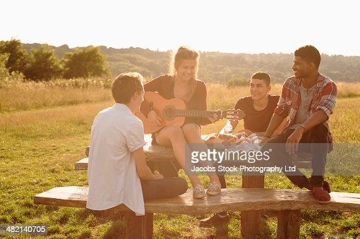 Friends playing music together at picnic table in rural field : Stock Photo