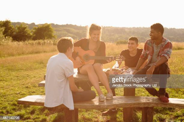 Friends playing music together at picnic table in rural field