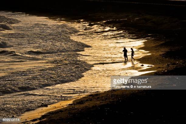 Friends playing on the sunset beach in Kamakura city in Kanagawa prefecture in Japan