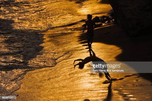Friends playing on the sunset beach in Kamakura in Kanagawa prefecture in Japan