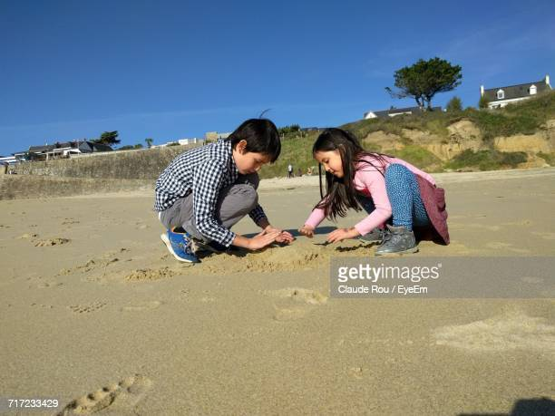 Friends Playing On Wet Sand At Beach Against Clear Blue Sky During Sunny Day