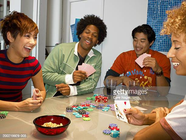 Friends playing poker in apartment, laughing