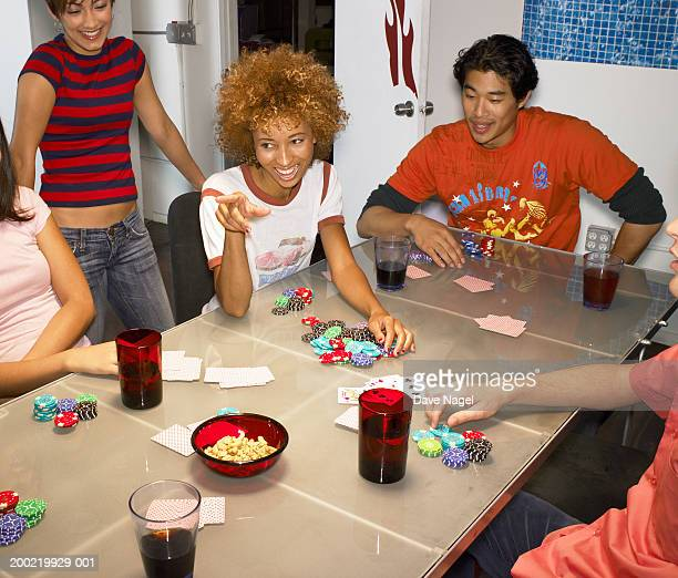 Friends playing poker in apartment, woman pointing finger