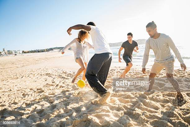 Friends playing soccer at the beach