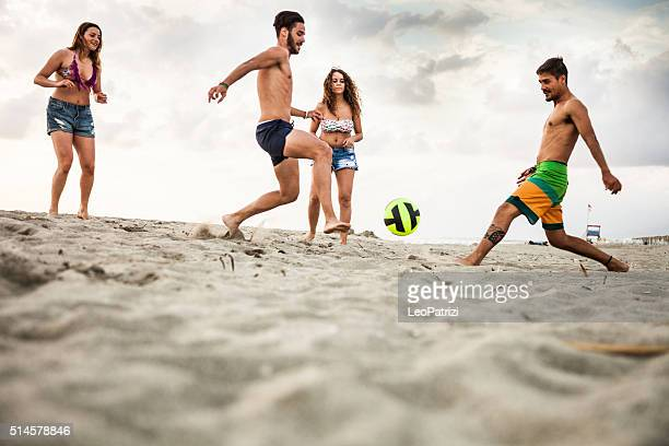 Friends playing soccer during vacations on the beach