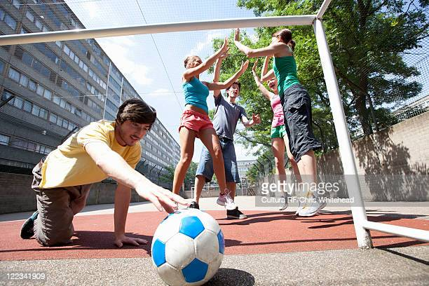 Friends playing soccer on city street