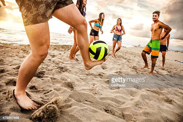 Friends playing soccer on the beach