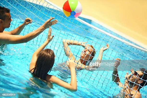 Amis, jouer au volley-ball dans la piscine.