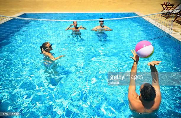 Amis jouant volleybay dans une piscine.