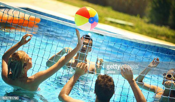 Friends playing volleybay in a pool.
