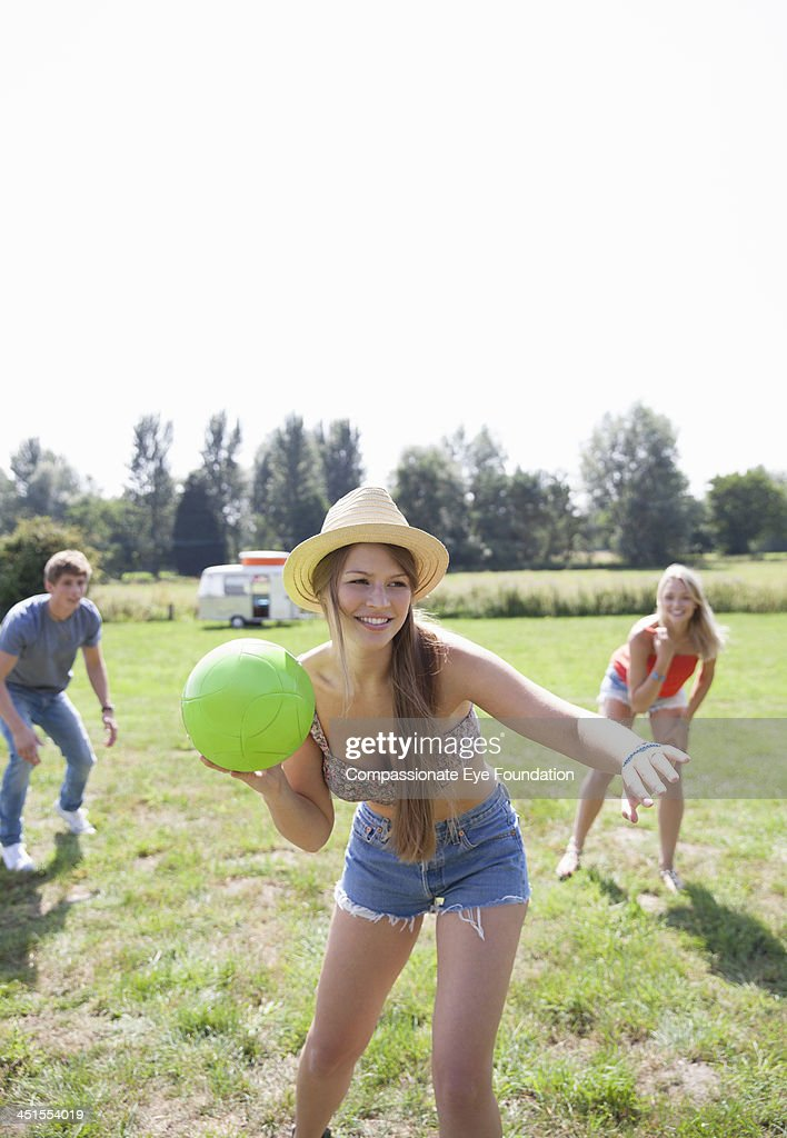 Friends playing with ball outdoors : Stock Photo