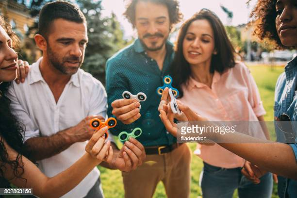 Friends playing with fidget spinners