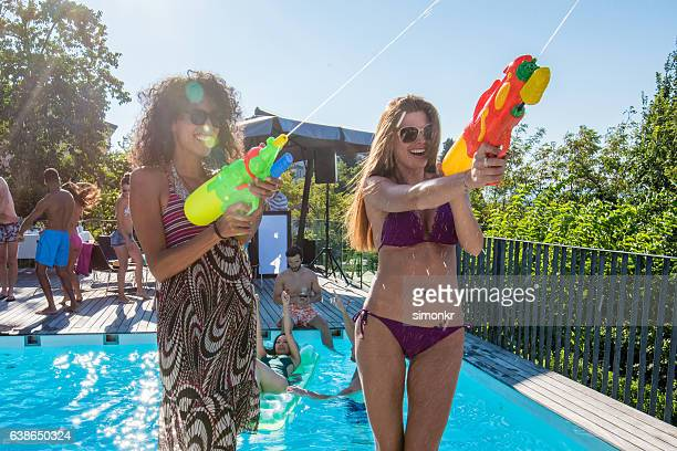 Friends playing with squirt guns