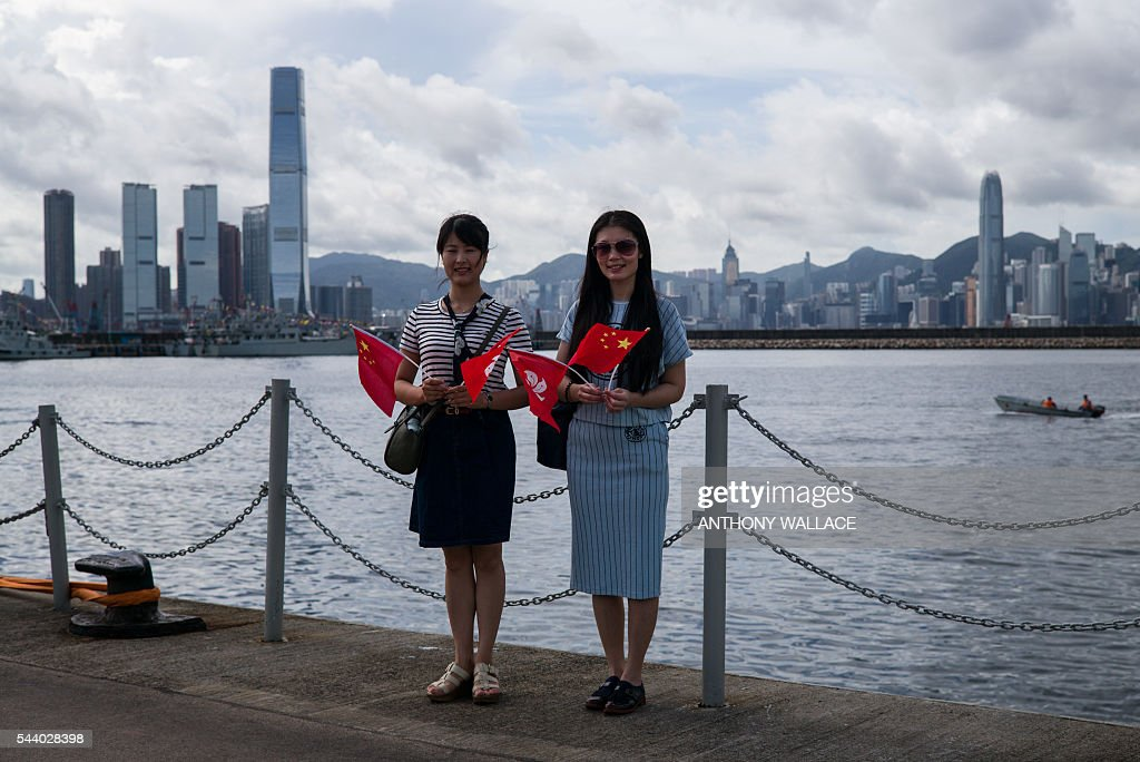 Friends pose for photos as they hold Chinese and Hong Kong flags during the open day of the Chinese People's Liberation Army (PLA) Navy Base at Stonecutter Island in Hong Kong on July 1, 2016, to mark the 19th anniversary of the Hong Kong handover to China . / AFP / Anthony Wallace