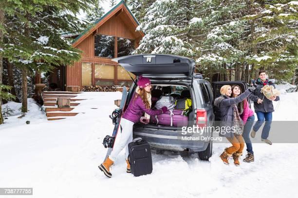 Friends posing for cell phone selfie near car in winter
