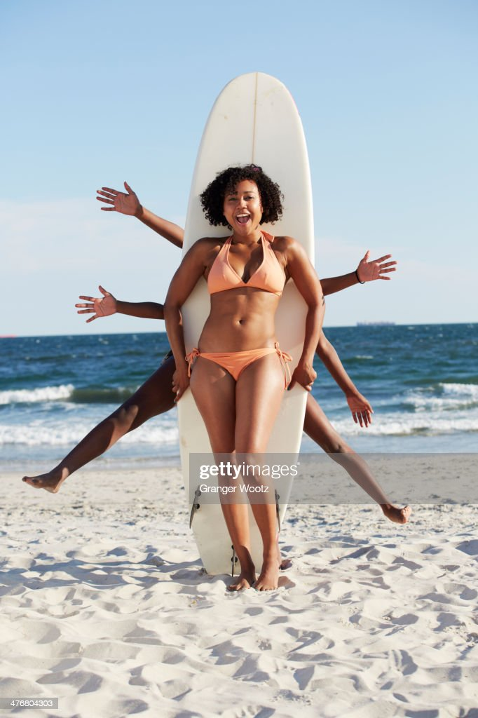Friends posing with surfboard on beach : Stock Photo