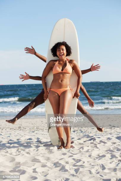 Friends posing with surfboard on beach