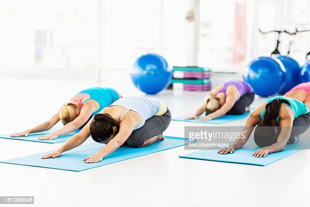 Friends Practicing Yoga In Gym