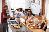 Friends Prepare And Serve Food For Dinner Party At Home Together