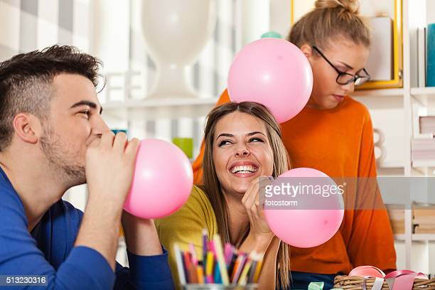Friends preparing balloons  for party