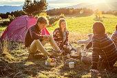 Friends preparing food at campsite