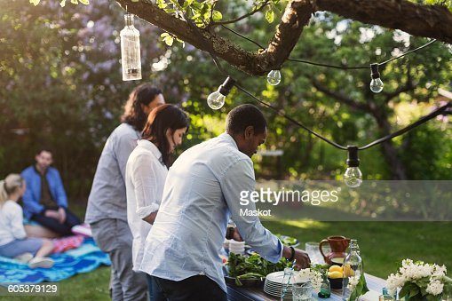 Friends preparing food at table in yard during summer party