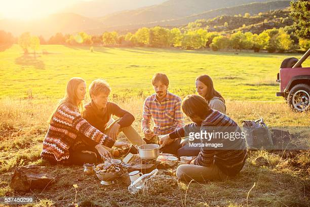 Friends preparing food on field