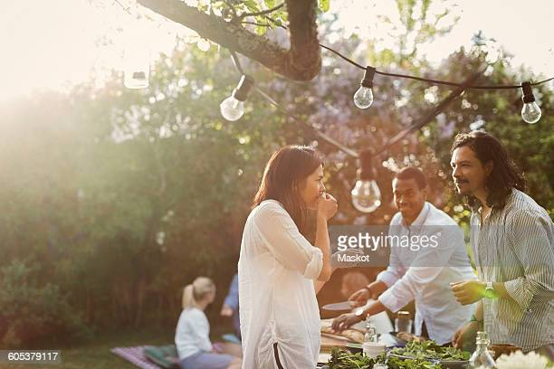 Friends preparing food together in backyard during summer party