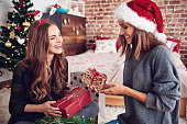 Friends presenting gifts each other in bedroom