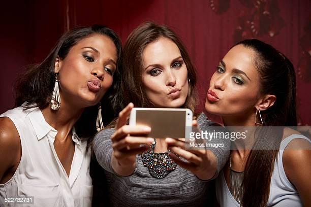 Friends puckering while taking selfie at nightclub