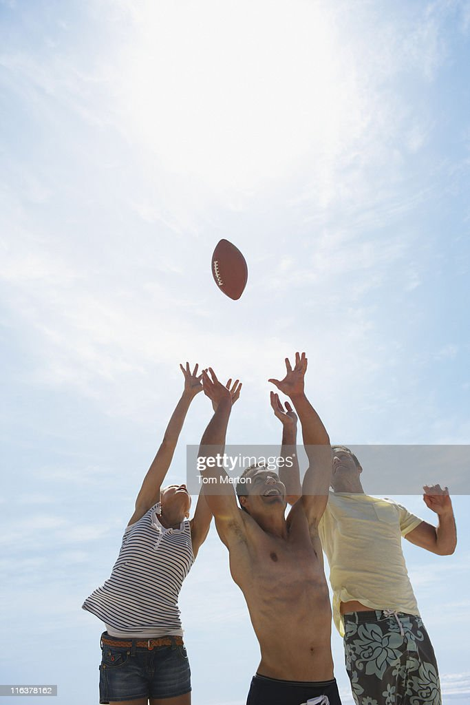 Friends reaching for football : Stock Photo