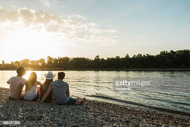 Friends relaxing at the riverside at sunset