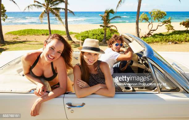 Friends relaxing in convertible on beach