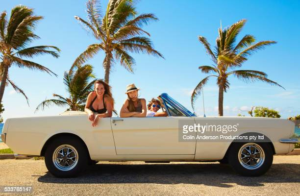Friends relaxing in convertible under palm trees